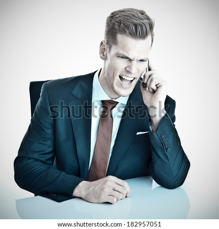 Angry young businessman screaming into his cellphone - stock photo