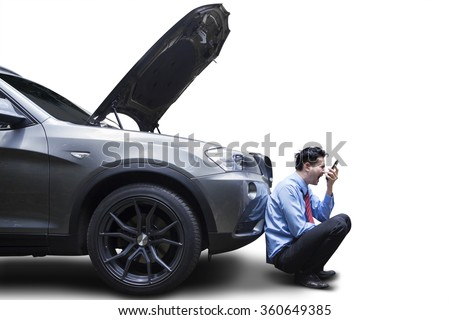 Angry young businessman using phone by broken down car, isolated on white background - stock photo