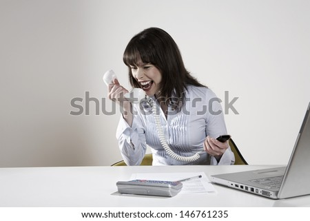 Angry young businesswoman screaming into phone receiver at desk - stock photo