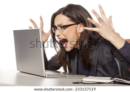 angry young businesswoman shouting at her laptop - stock photo