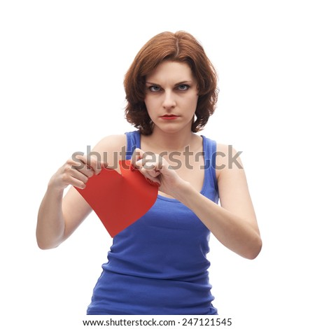 Angry young caucasian woman in her twenties tearing red heart in two halves, composition isolated over the white background - stock photo