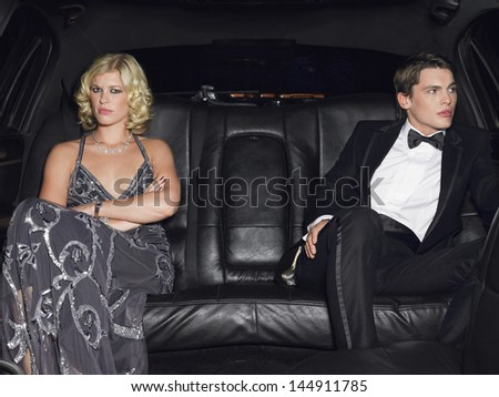 Angry young couple in limousine after breaking up - stock photo