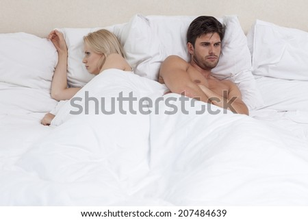 Angry young couple lying in bed