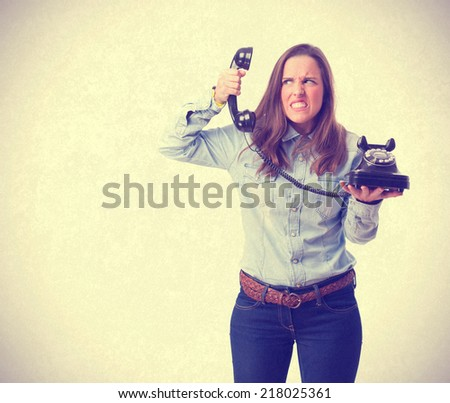angry young girl holding a phone. isolated - stock photo