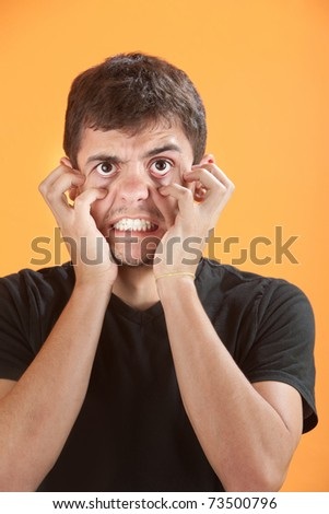 Angry young Latino teen on an orange background - stock photo