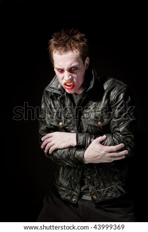 Angry young male zombie in black leather jacket - stock photo