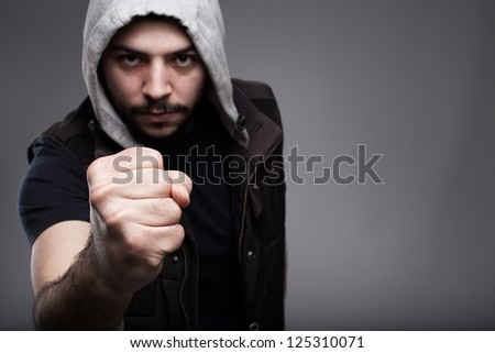 angry young man challenging.shallow depth of field where fist in focus and model's face is out of focus.