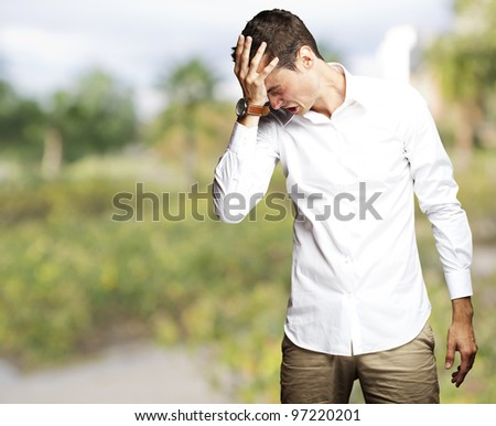 Angry young man doing a frustration gesture at park - stock photo