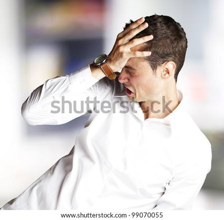 Angry young man doing frustration gesture indoor - stock photo