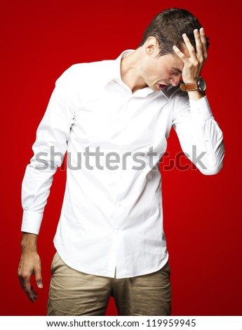 Angry young man doing frustration gesture over red background - stock photo