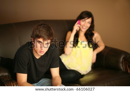 angry young man feeling ignored by beautiful girlfriend on phone - stock photo
