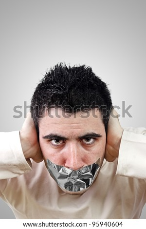 Angry young man having gray duct tape on his mouth.Gradient background with copy space.