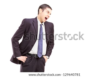 Angry young man in a suit shouting - stock photo