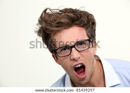 Angry young man in glasses - stock photo