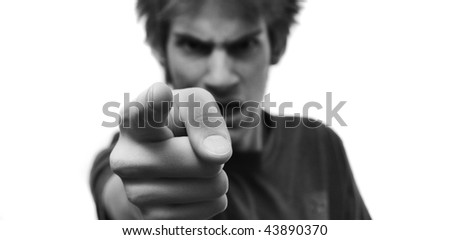 Angry young man pointing his finger with rage at the camera. The hand is selectively in focus and there is white isolated copyspace on both sides of him. - stock photo