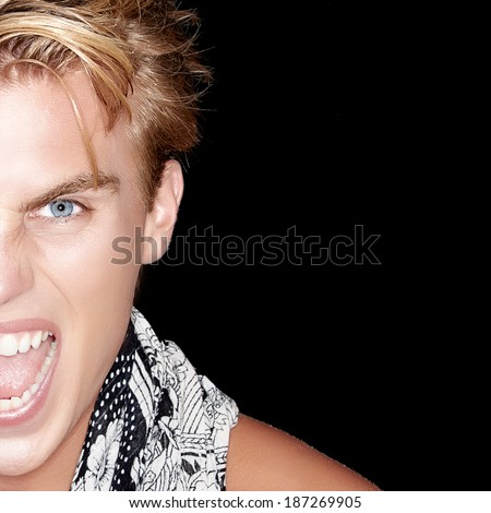 Angry young man screaming. Closeup portrait isolated on black.  Man half face portrait - stock photo