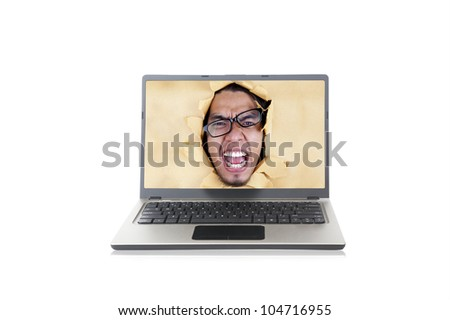 Angry young man with glasses on the screen of ultrabook laptop computer - stock photo