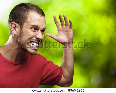 angry young man with plants as a background - stock photo