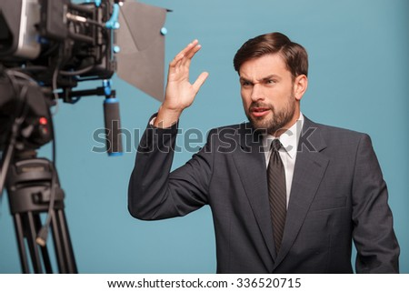Angry young tv newscaster is standing and speaking to the camera at studio. He is looking at the technology with aggression and gesturing. Isolated on blue background - stock photo