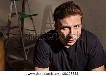 Angry young white man with ladder in background - stock photo