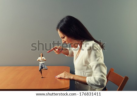 angry young woman screaming and pointing at small calm woman - stock photo