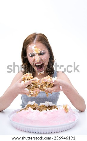 Angry young woman sitting at the table with cake at her face - stock photo