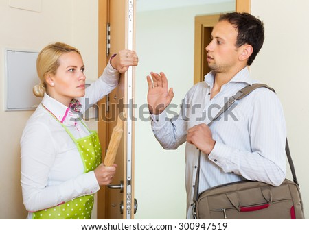 Angry young woman threatens with rolling-pin for a frightened man - stock photo