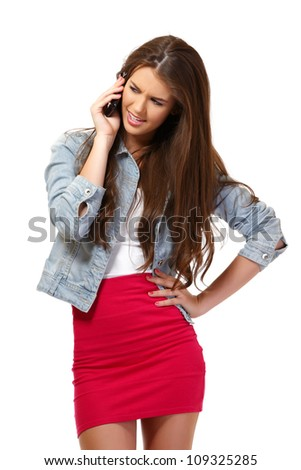 angry young woman with cellphone in studio - stock photo