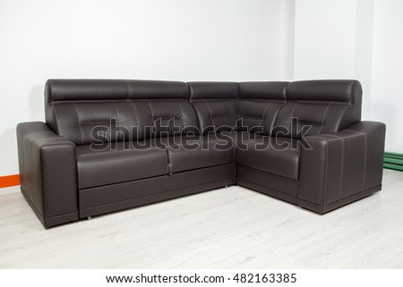 angular black leather sofa on a neutral background