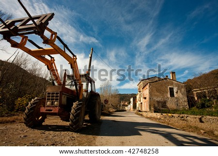 Angular view of a tractor and a rural home.