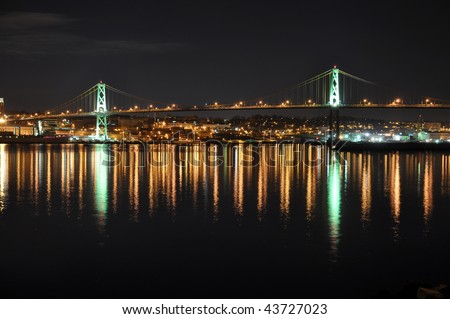 Angus L. Macdonald Bridge that connects Halifax to Dartmouth, Nova Scotia. Taken in December at night with reflections in water - stock photo