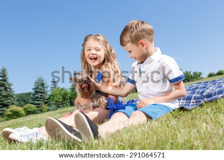 Animal lovers.  Vivacious bright little children palming the dog while playing with it and sitting on blanket. - stock photo