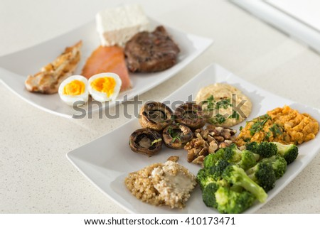 animal versus plant proteins: one plate with beef, eggs, salmon, cheese and chicken grill and another with nuts, mushrooms, broccoli, lentil, hummus and quinoa - stock photo