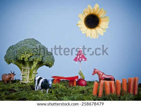 Animals on creative farm or garden made of vegetables: broccoli tree, dill grass, red pepper bench, carrot fence and sunflower sun, concept. - stock photo