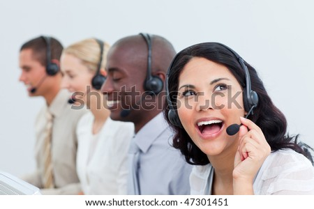 Animated businesswoman and her team working in a call center in the office - stock photo