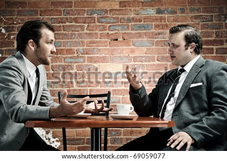 Animated debate between two vintage coffee connoisseurs - stock photo