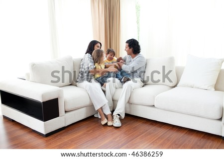 Animated family having fun sitting on sofa at home - stock photo