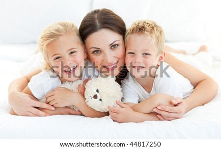 Animated siblings with their mother lying on a bed at home