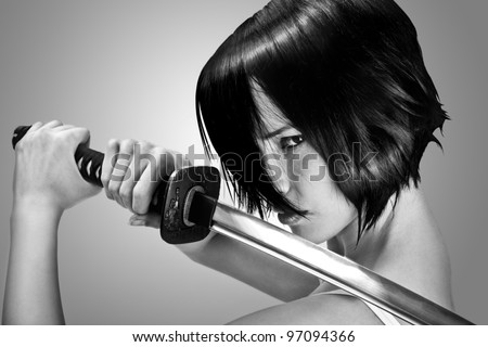 Anime stylized brunette with short hair watching with stern look holding a katana sword with two hands - stock photo