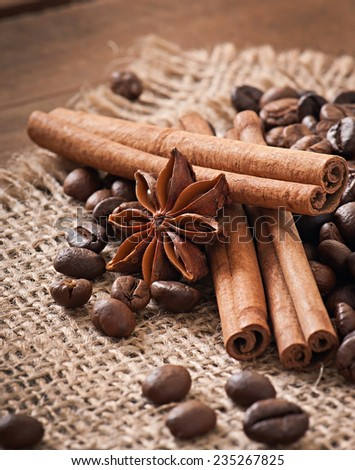 Anise, cinnamon and coffee beans on old wooden background - stock photo