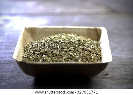 Anise seeds on wooden bowl on a wooden table