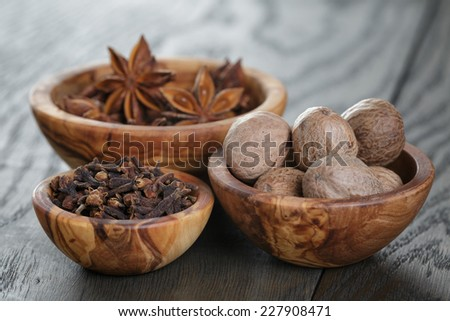anise stars, cloves and nutmeg on oak table, christmas spices - stock photo