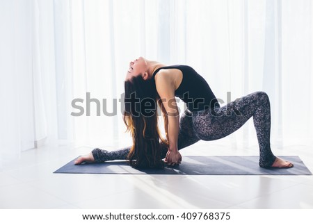 Anjanejasana. Beautiful yoga woman practice in a training hall background. Yoga concept. - stock photo