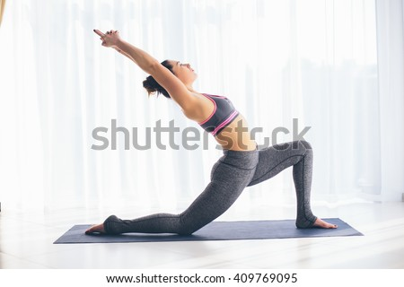 Anjaneyasana. Beautiful yoga woman practice in a training hall background. Yoga concept. - stock photo