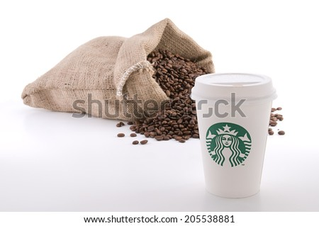 Ankara, Turkey - June 07, 2012:  Cup of Starbucks coffee with cup sleeve in front of sack of coffee beans isolated on white background - stock photo