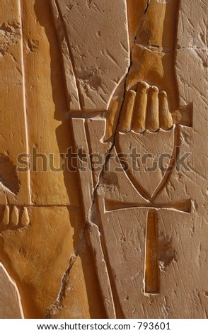 Ankh, an ancient Egyptian symbol of life, in hand of a god, on the wall of the temple of Queen Hapshepsut near Luxor (Thebes), Egypt. - stock photo