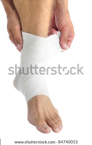 Ankle of male athlete being wrapped with white bandage