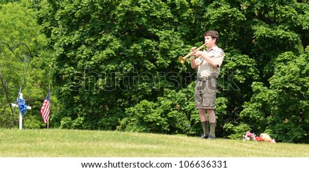 ANN ARBOR, MI - MAY 27: An unidentified boy scout plays taps at the annual Memorial Day observance on May 27, 2012 at Arborcrest Memorial Park in Ann Arbor, MI - stock photo