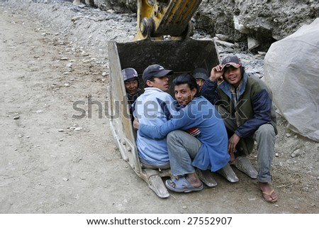 ANNAPURNA, NEPAL – MARCH 30: Young road construction workers protect themselves from the cold winds after a day's work in Annapurna, Nepal March 30, 2008.