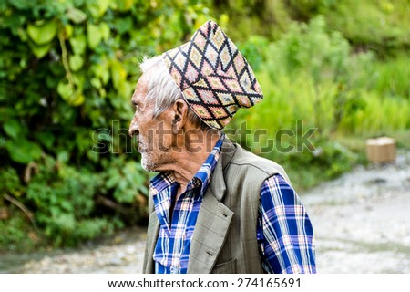 ANNAPURNA, NEPAL - OCTOBER 8, 2014: Old Nepali man looking sideways with traditional hat on dirt road in Annapurna.  - stock photo
